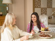 Old woman is having tea with a daughter stock image