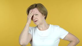 Old Woman with Headache Isolated on Yellow Background stock video