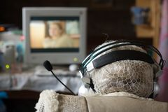 Old woman with headphones. Watching TV Stock Images