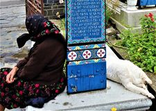 Old woman in traditional clothes sits on a grave with a dog sleeping at Cimitirul Vesel Merry Cemetery in Sapanta village, Romania royalty free stock photo