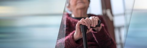 Old woman with her hands on a cane. panoramic banner royalty free stock photography