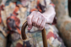 Old woman with her hands on a cane Royalty Free Stock Image