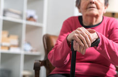 Old woman with her hands on a cane Stock Image