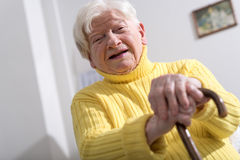 Old woman with her hands on a cane Stock Photo