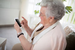Old woman and her smartphone Royalty Free Stock Photography