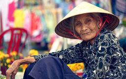 Old woman, Hoi An, Vietnam. Profile portrait of old woman in traditional hat selling flowers on streets of Hoi An, Vietnam stock photo