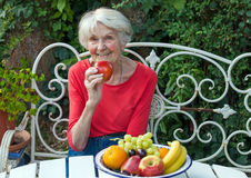 Old Woman Holding an Apple at the Garden Table Stock Photo