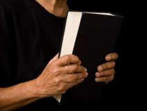 Old woman holding bible. An old woman holds a bible in prayer Stock Photo