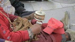 Old woman holding buddhist prayer wheel stock video