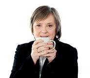 Old woman holding coffee mug Royalty Free Stock Images
