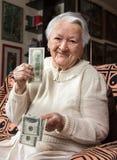 Old woman holding dollar cash money Stock Photo