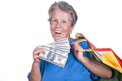 Old woman holding dollars and bags Royalty Free Stock Images