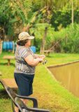 Old woman holding a fishing rod, hooking a fish on a lake. Stock Photos