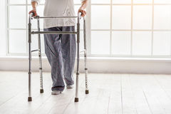 Old woman holding foldable walker and moving in hospital Stock Photos