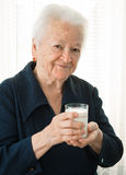 Old woman holding a glass milk Stock Photo