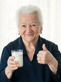 Old woman holding a glass milk Stock Photography