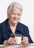 Old woman holding a glass milk Royalty Free Stock Photography