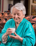 Old woman holding a glass milk Stock Photos