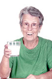 Old woman holding a glass of milk. On white background Stock Photo