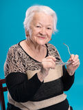 Old woman holding glasses Royalty Free Stock Photo