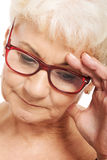 An old woman holding her head, thinking/ worrying. Stock Photography
