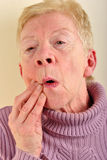 Old woman holding her painful jawbone Royalty Free Stock Photo