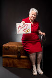 Old woman holding Marry Me board stock photography