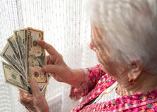 Old woman holding money in hands Royalty Free Stock Image
