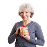 Old woman holding piggy bank Royalty Free Stock Images