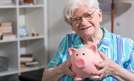 Old woman holding a piggy bank Stock Photo