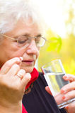 Old woman holding a pill in her hand Royalty Free Stock Photography