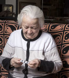 Old woman holding pills. At home Royalty Free Stock Images