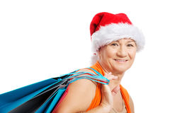 An old woman holding presents/bags in santa hat. Royalty Free Stock Photo