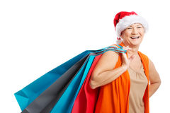 An old woman holding presents/bags in santa hat. Stock Photos