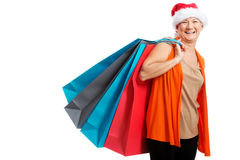 An old woman holding presents/bags in santa hat. Stock Photo