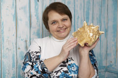 Old woman holding a seashell. Selective focus on her face. Stock Image