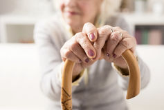 Old woman holding on to walking stick stock images