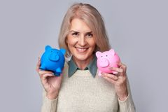 Old woman holding two piggy banks. Smiling old woman holding two piggy banks. Isolated on grey Stock Photo