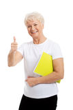 An old woman holding workbook and showing OK. Royalty Free Stock Photography