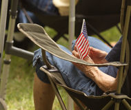 Old woman holds flag at Tea Party Rally. Old woman in a lawn chair holds a small American Flag at a Tea Party rally sponsored by Nebraska Taxpayers for Freedom Royalty Free Stock Photography