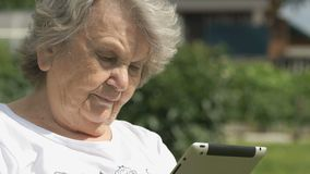 Old woman holds a silver computer tablet outdoors stock video footage