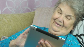 Old woman holds a tablet computer indoors stock footage