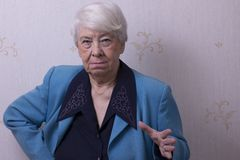 Old woman at home. Angry Stock Photo