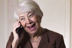 Old woman at home. Calling Stock Images