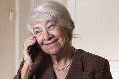 Old woman at home. Calling Royalty Free Stock Photography