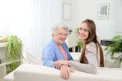 Old woman at home with cheerful young girl spending time together with laptop computer Stock Photos