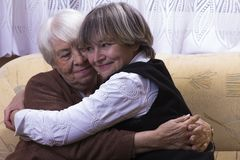Old woman at home with daughter. Old women at home with daughter hugging Royalty Free Stock Images