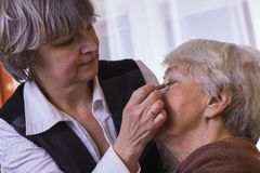Old woman at home with daughter. Old women at home with daughter while make up Stock Photo