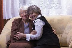 Old woman at home with daughter. Old women at home with daughter smiling Royalty Free Stock Photo