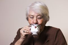 Old woman at home. Drinking tea Stock Images